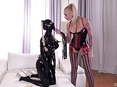 Mistress plays median with slave girl dressed in latex costume
