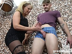Aged woman gives a blowjob and tugjob to young guy in burnish apply sauna